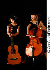 Young Musicians - School aged girls with cello and guitar on...