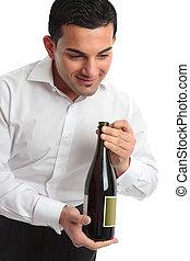 Waiter presenting bottle of wine - A waiter or servant...