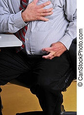 Man having heart attack at his desk - Middle aged,overweight...