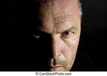 Low key portrait of menacing looking caucasian man - Dark...