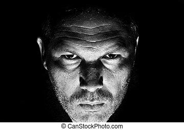 Low key portrait of menacing looking caucasian man - Dark...