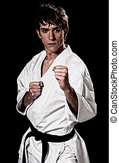 Karate male fighter young high contrast on black background....