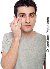 Young man applying eye cream - handsome young man applying...