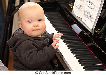 Baby and piano - Portrait of a baby trying to play piano