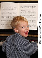 Young piano player - Portrait of a happy young boy playing...