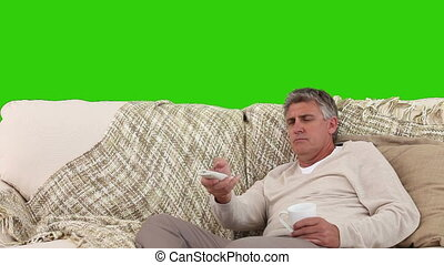 Retired man holding a cup of tea on his sofa - Chromakey...