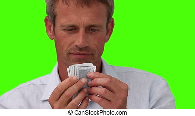Casual man playing cards against a green screen