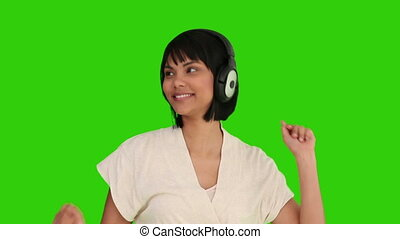 Beautiful asian woman is listenning to music against a green...