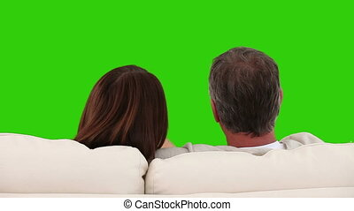 Retired couple watching tv on a sofa - Chromakey footage of...