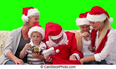 Christmas with Santa Claus in a family against a green...