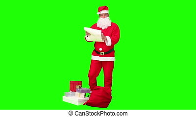 Santa Claus checking his list of gift against a green screen