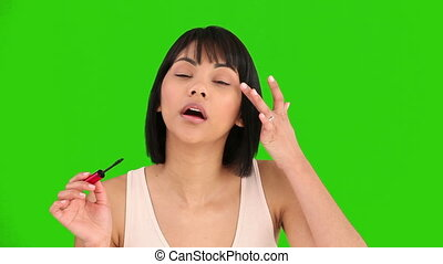 Coquette asian woman putting on make-up - Chromakey footage...