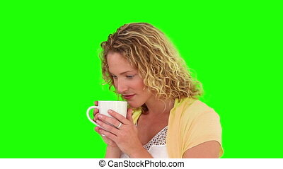 Curly-haired woman drinking a cup of tea against a green...