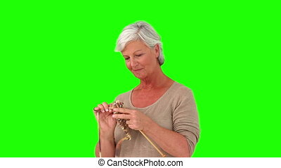 Retired woman knitting against a green screen