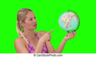Blond woman in purple swimsuit playing with a world globe