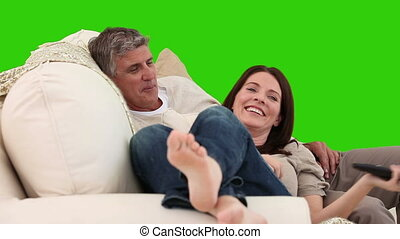 Couple having a good time on the sofa against a green screen