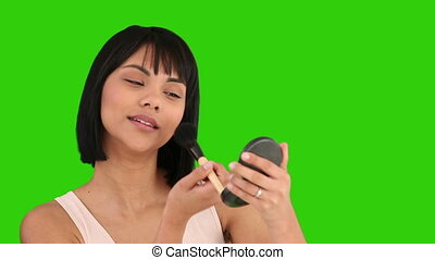 Asian woman with a mirror putting on make-up against a green...