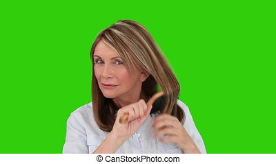 Retired woman is fixing her hair against a green screen