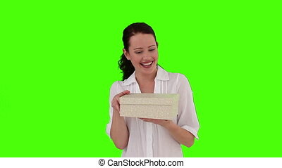 Dark-haired woman opening a present against a green screen