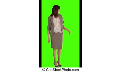 Woman in suit looking at the camera against a green screen