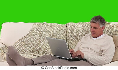Mature man laughing in front of his laptop against a green...