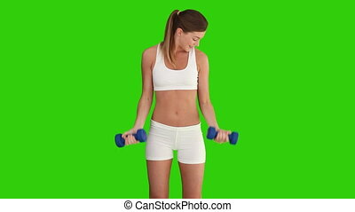 Pretty brown-haired lady in sportswear doing exercice with dumbbells