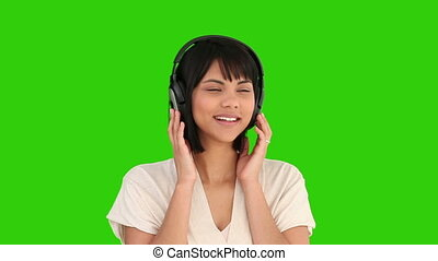 Asian woman listenning to music - Chromakey footage of an...