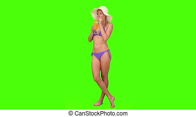 Blond lady in swimsuit with an hat sipping a cocktail