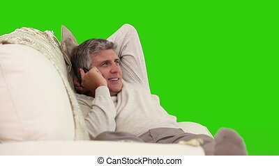 Casual retired man having a phone call on his sofa against a...