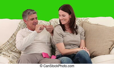 Retired man giving a present to his wife against a green...