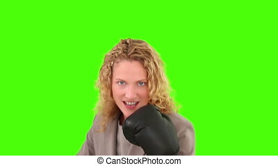 Curly blond haired woman with box gloves against a green...