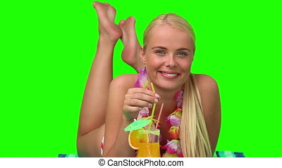 Wonderful blond woman on the beach sipping a cocktail -...