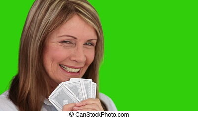 Retired woman playing cards against a green screen