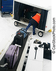 loading baggage - an airline baggage handler loading baggage...