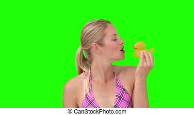 Blond woman in purple swimsuit playing with a plastic duck...