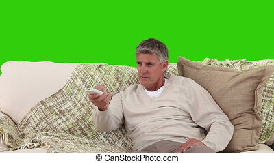 Retired man with a remote control on his sofa against a...