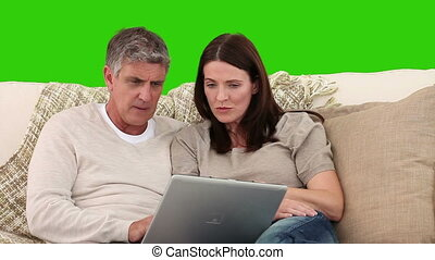 Retired couple looking at a laptop on a sofa