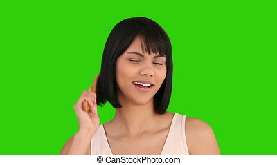 Pretty asian woman fixing her  hair against a green screen