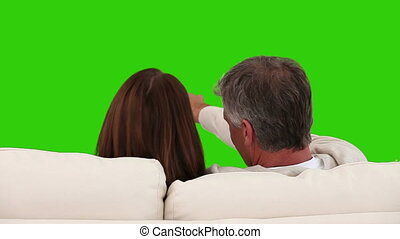 Retired couple watching tv on a sofa against a green screen