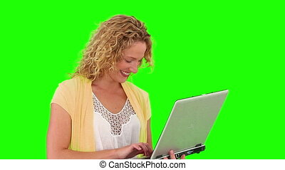 Curly blond haired woman using a laptop - Chromakey footage...