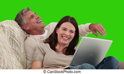 Retired couple using a laptop on their sofa against a green...