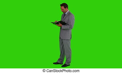 Young businessman taking note - Chroma-key footage of a...