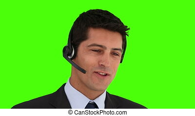 Dark-haired businessman speaking over the headset against a...