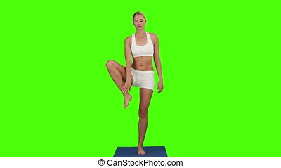 Lady in sportswear doing yoga against a green screen