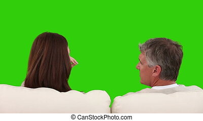 Retired couple talking on a sofa against a green screen