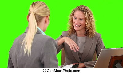 Blond women having a meeting against a green screen