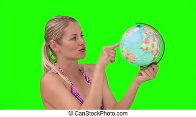 Blond woman in swimsuit chosing her destination with a world globe