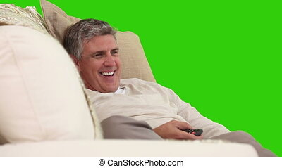 Senior man laughing on his sofa