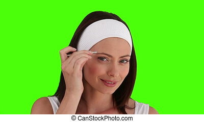 Dark-haired woman plucking off her eyebrows against a green...