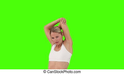 Blond woman in sportswear stretching her against a green...